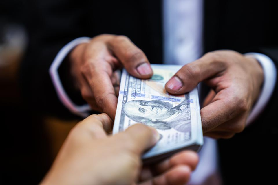 Businessman giving bribe money  to partner in a corruption scam with black  tone,corruption