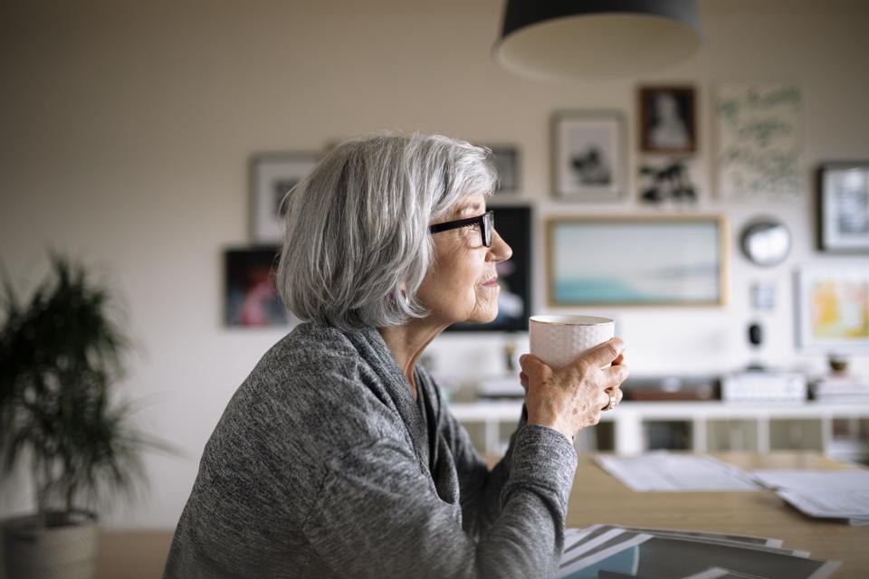 Thoughtful female senior designer drinking coffee in office