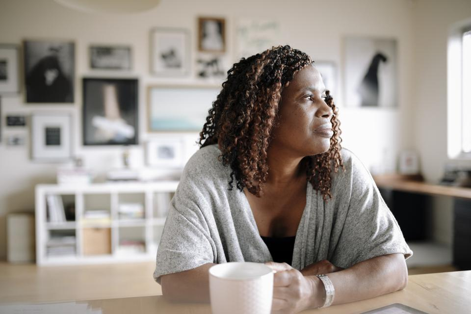 Thoughtful businesswoman drinking coffee in office