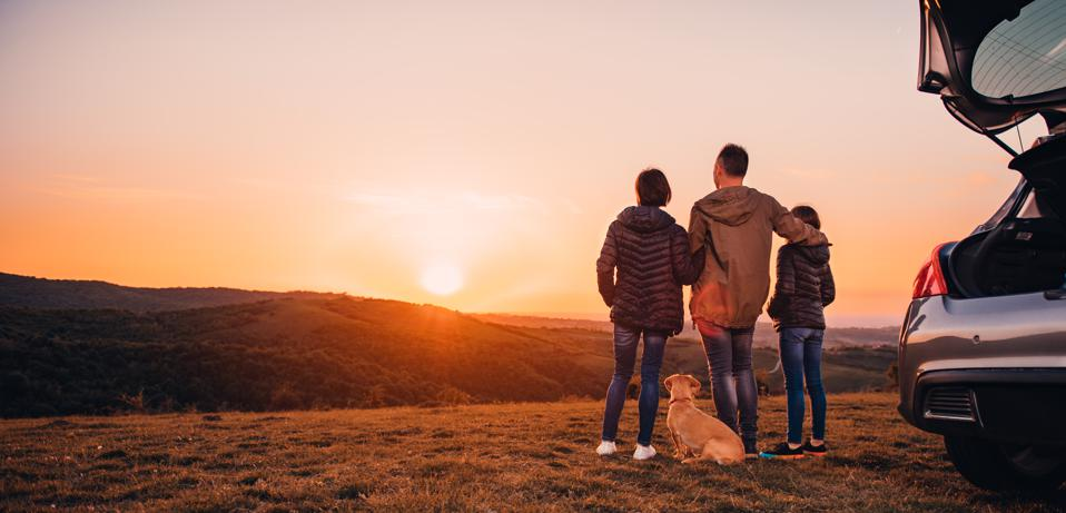Family with dog hugging on the hill and looking at sunset