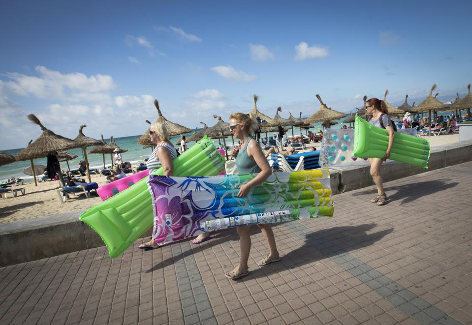 British tourists enjoy a sunny day at the Playa de Palma beach in Palma de Mallorca, Spain.