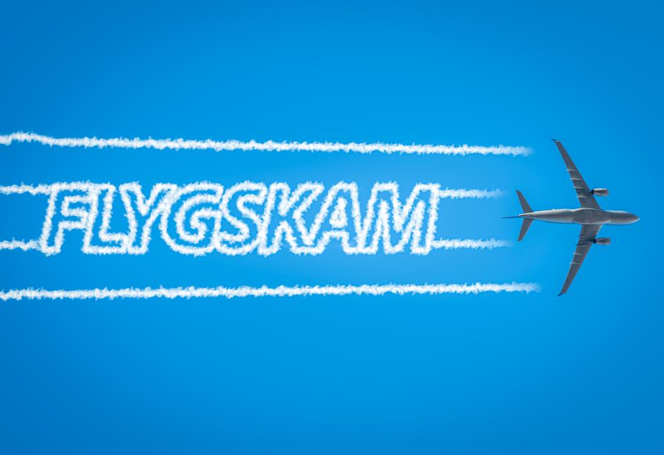 Airplane leaving jet contrails with Flygskam word inside