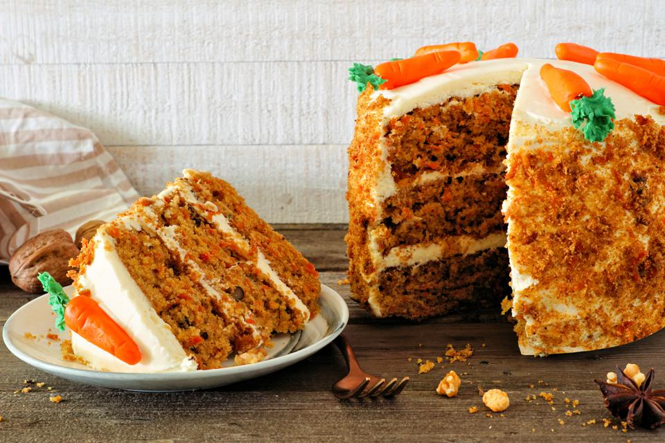 Slice of homemade carrot cake with cream cheese frosting, side view table scene against white wood
