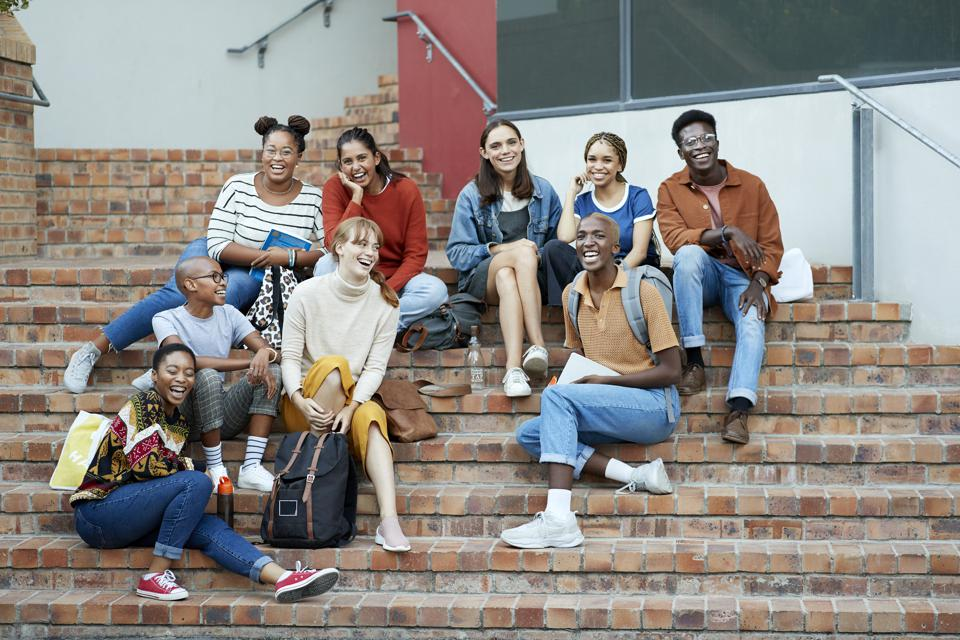 Smiling young Gen-Z university students sitting on steps, preparing for their future in a post-pandemic world