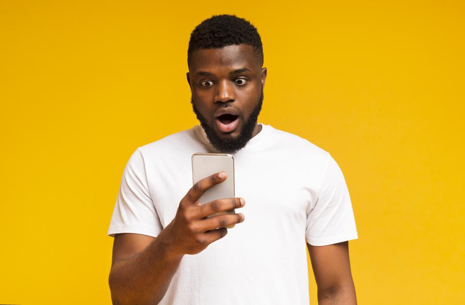 Shocked african man looking at smartphone screen in amazement
