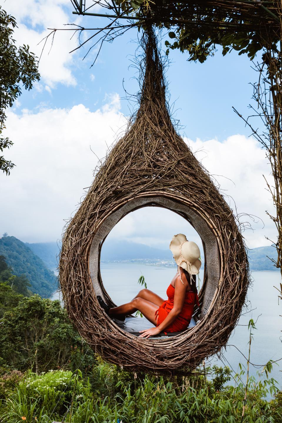 Woman inside a swing nest over lake, Munduk, Bali