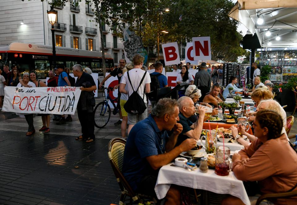Tourists at restaurant in La Rambla in Barcelona and protesters saying 'go home'