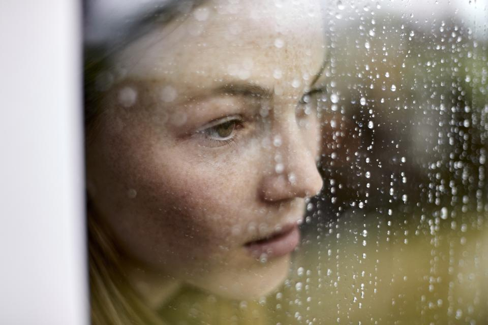 Close-up of pensive young woman looking out of window