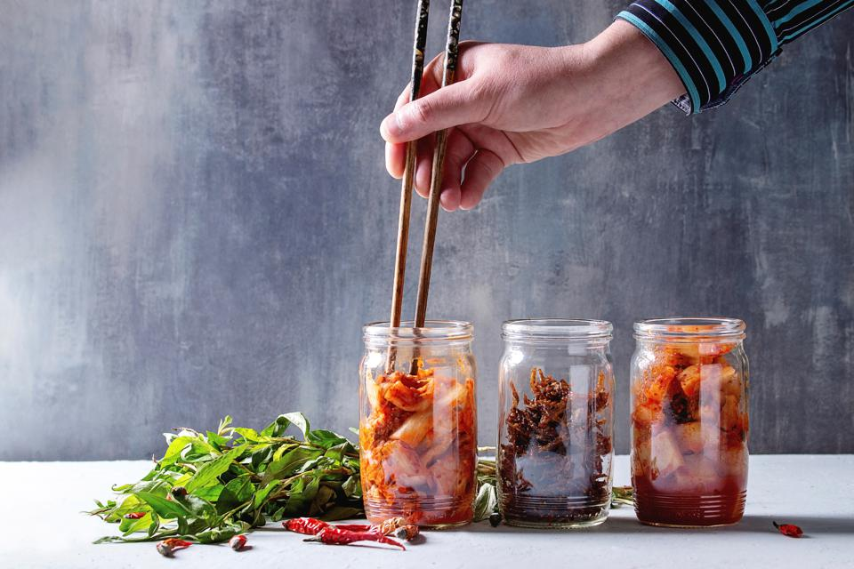 Korean traditional fermented appetizer kimchi cabbage and radish salad. fish snack served in glass jars with Vietnamese oregano and chili peppers over grey blue table. Chopsticks in mans hands.