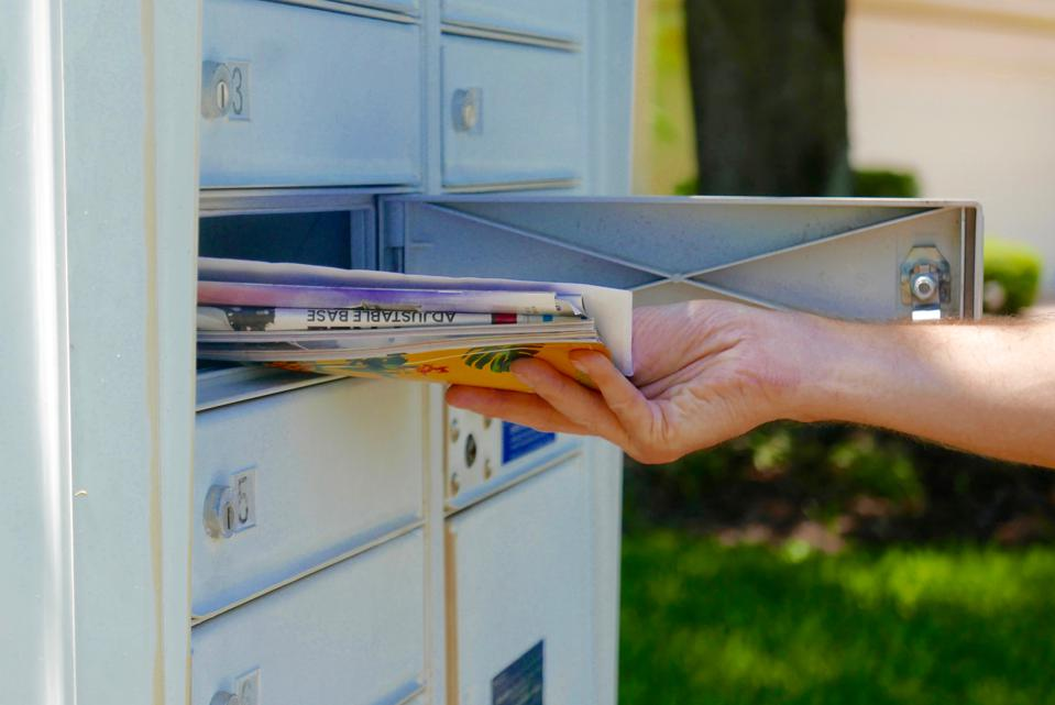 Person's hand pulling mail out of a mailbox