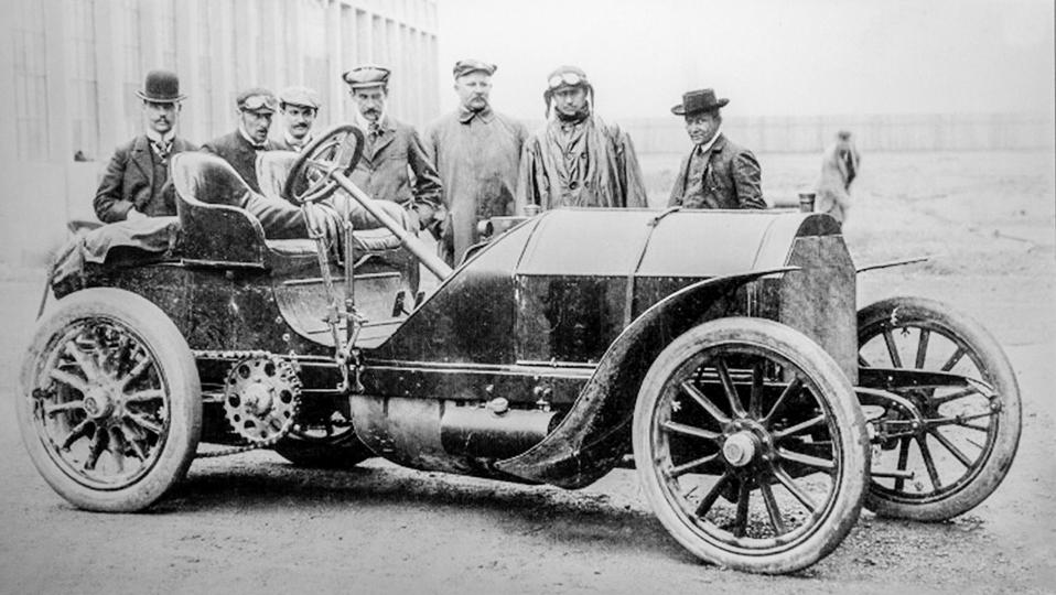 Old archival black and white photograph showing factory-backed driver