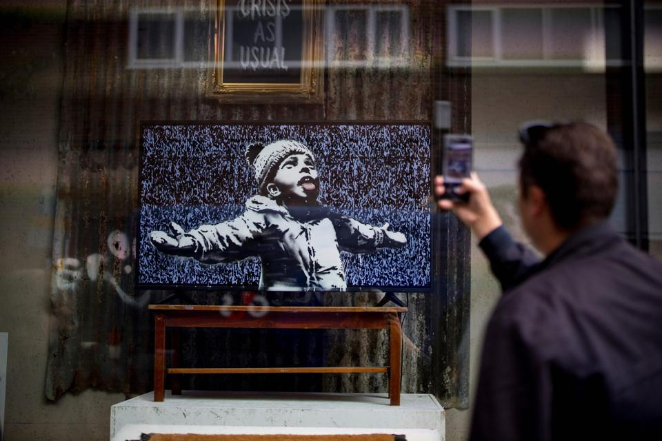 A man takes a photograph of Banksy's  'Gross Domestic Product' shop in London.