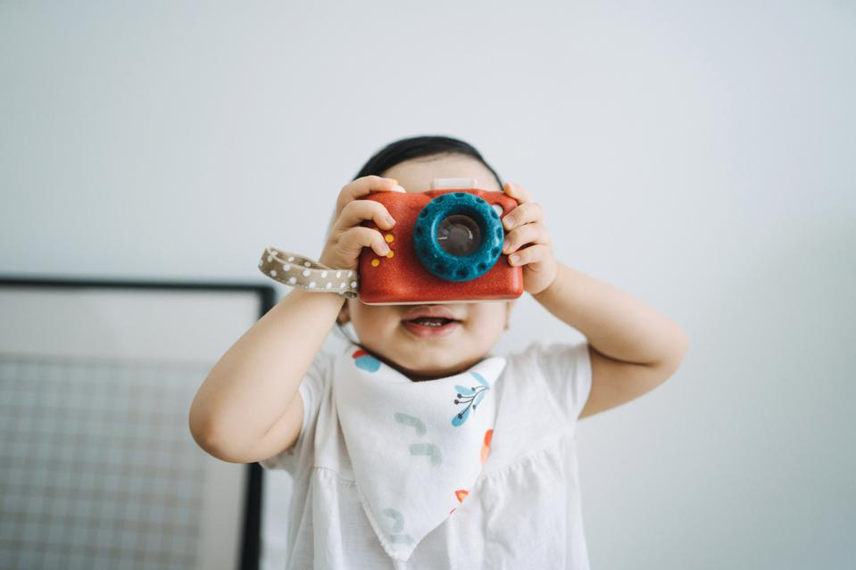 Cute little toddler girl having fun and taking photos with toy camera at home