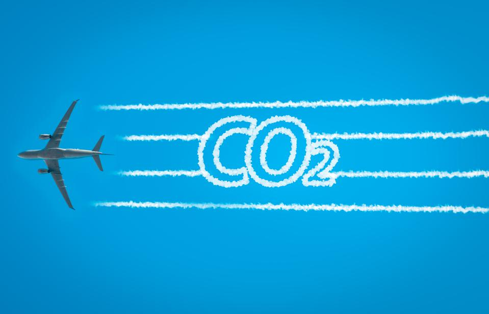 Airplane leaving jet contrails with CO2 word inside