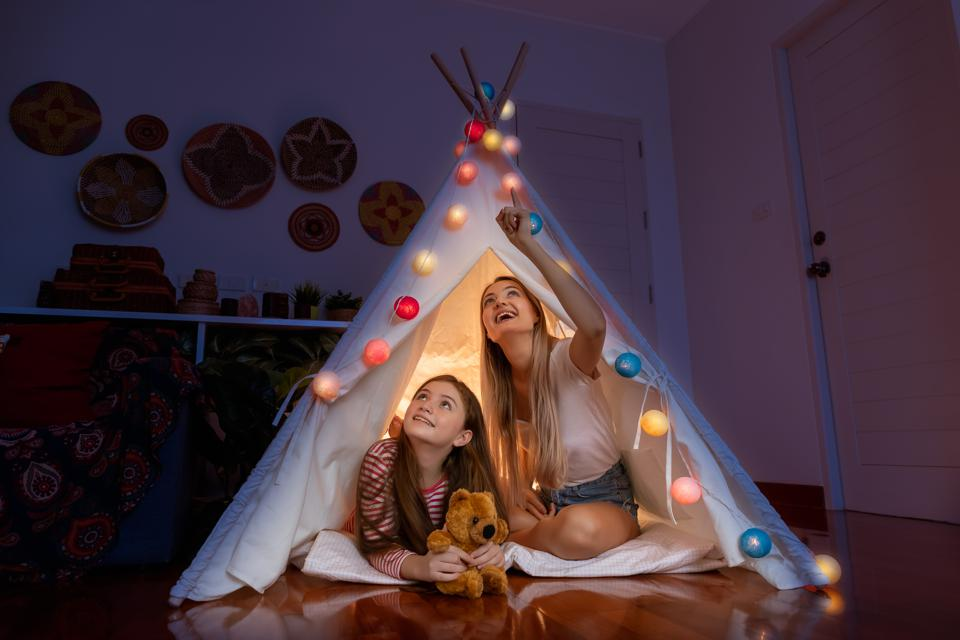 Happy mother and daughter inside tepee tent in bedroom, looking and pointing ceiling counting stars; family relationship concept.