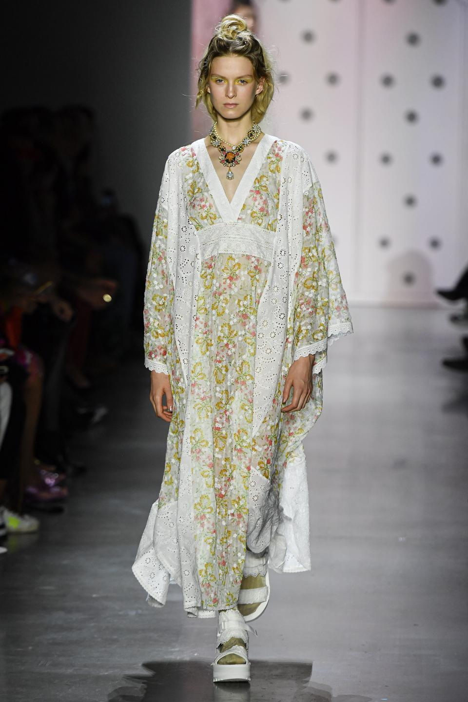 A model wearing Anna Sui's a look from the Spring 2020 Runway collection, a floral long dress with matching robe style jacket