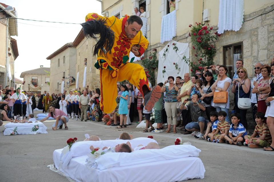 Man jumping over babies  during El Colacho Festiva in Spain.
