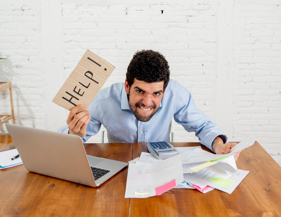 Young overwhelmed entrepreneur needing help paying off debts and bills in Small business financial problems. Worried desperate young man feeling stressed working through finances at home office.