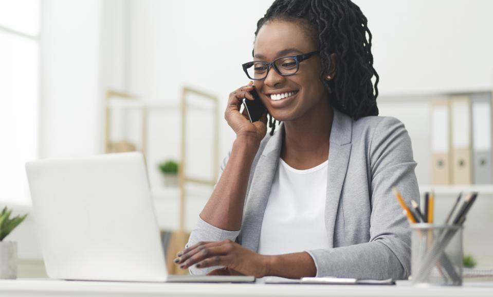 Happy Business Girl Having Phone Conversation Using Laptop In Office
