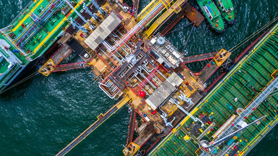 Aerial top view of two fuel tanker ship at the port, Oil terminal is industrial facility for storage of oil and gas petrochemical products ready for transport to further storage facilities.