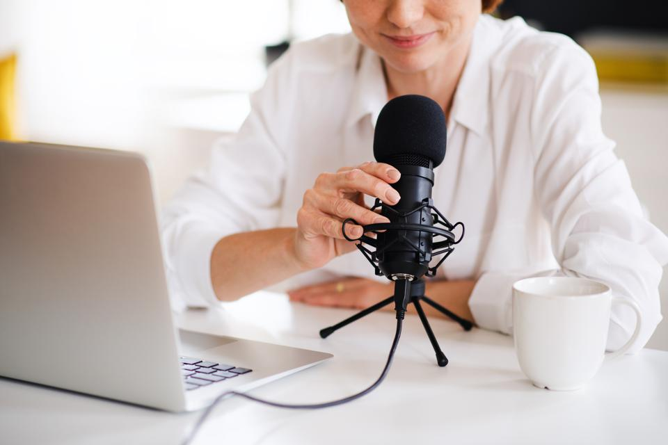 Midsection of woman vlogger or blogger with laptop and microphone, talking.