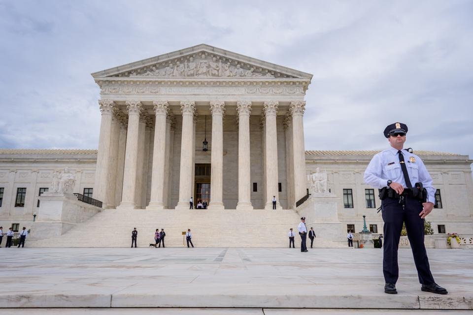 A police officer guarding outside the Supreme Court of the...