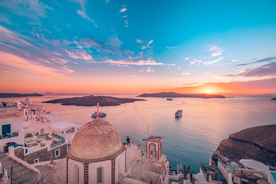 View of Fira, caldera, Santorini, Greece with cruise ships at sunset. Coronavirus.