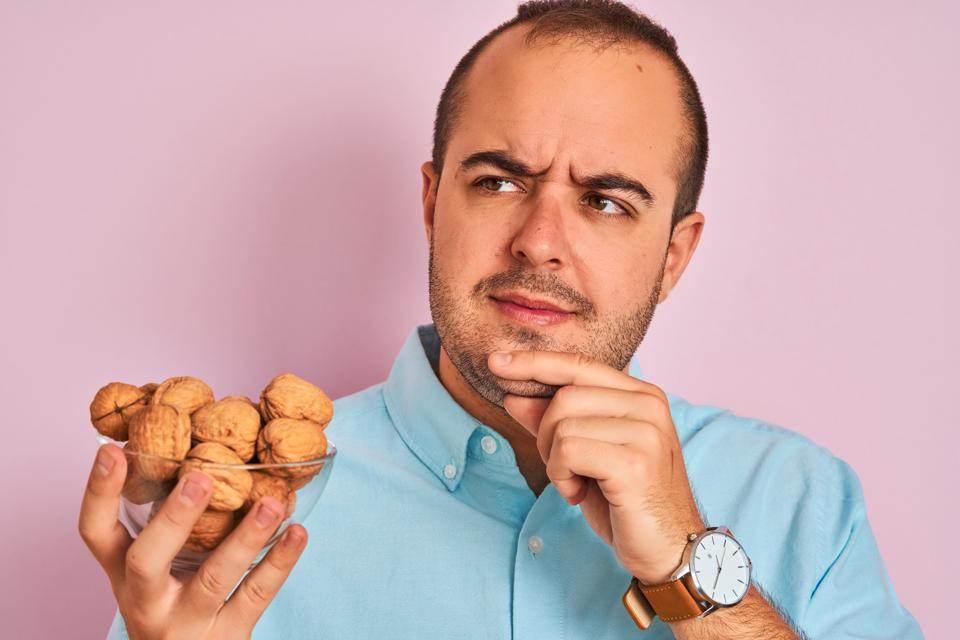Young man holding bowl with walnuts standing over isolated pink background serious face thinking about question, very confused idea