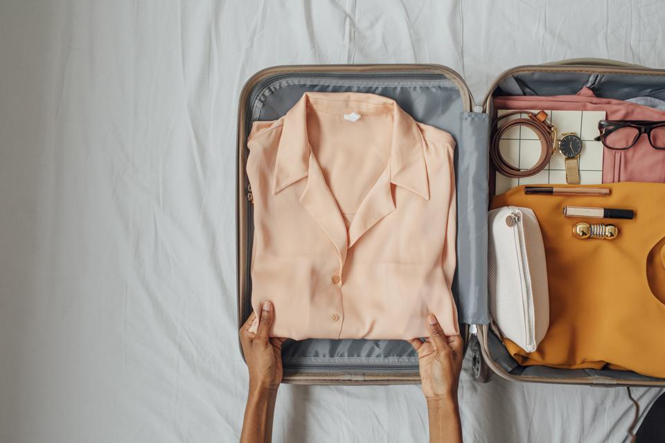 A Woman Packs Her Clothes in a Suitcase