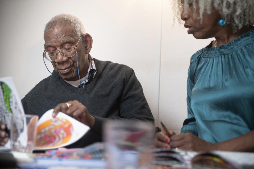 91 year old man colouring at home with his 62 year old daughter
