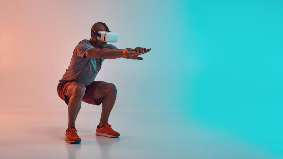Full length of young african man in sports clothing doing squat while wearing virtual reality glasses