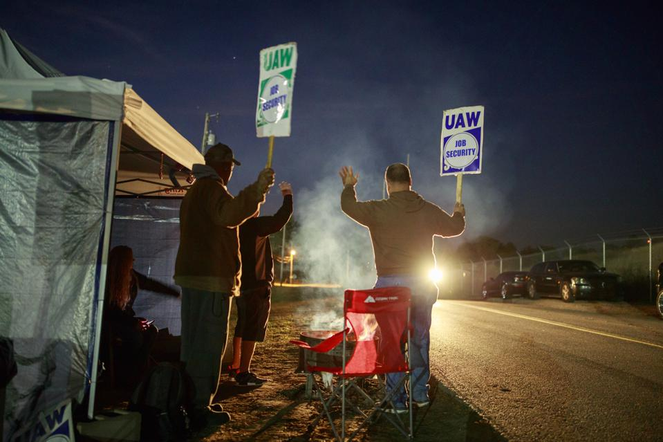 Workers wave to a passing motorist as United Auto Workers (...