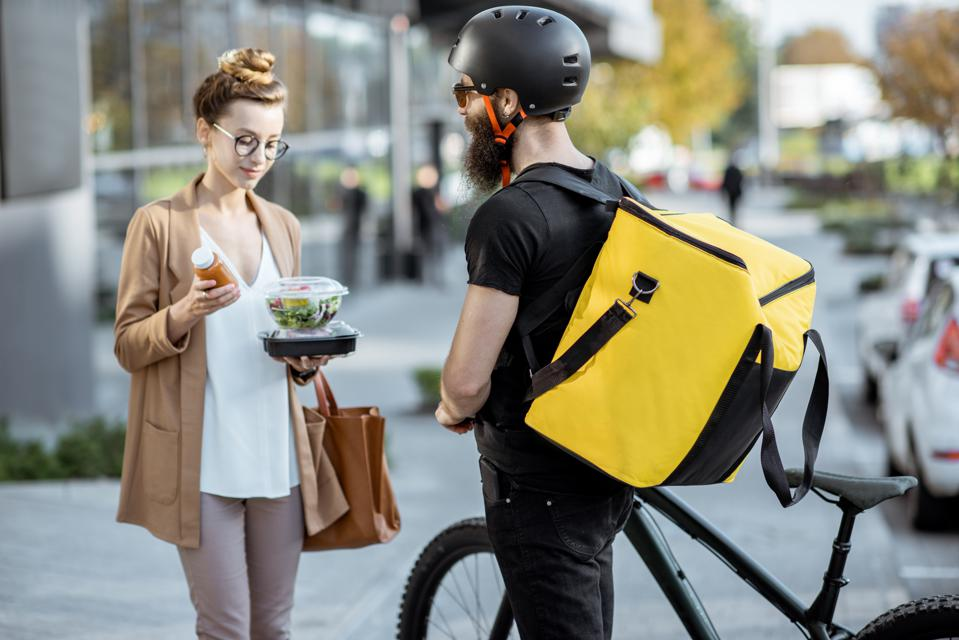 Courier delivering food to a business woman outdoors