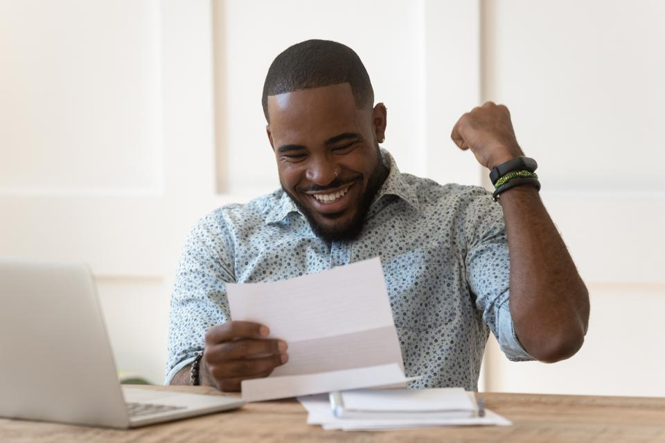Happy african american guy received banking loan approval.