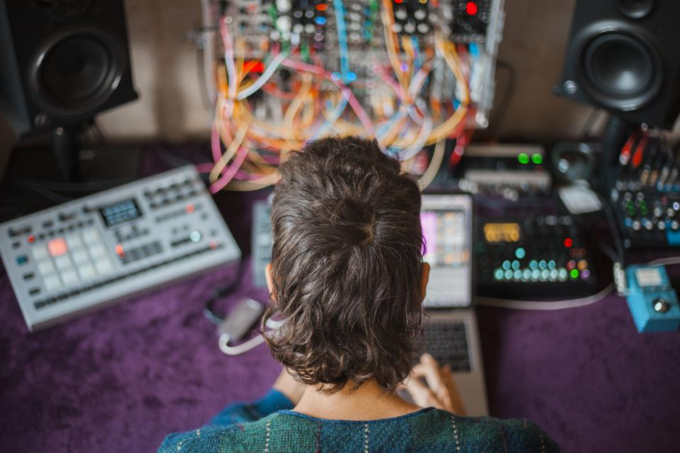 Rear view of an electronic music producer in studio mixing sounds