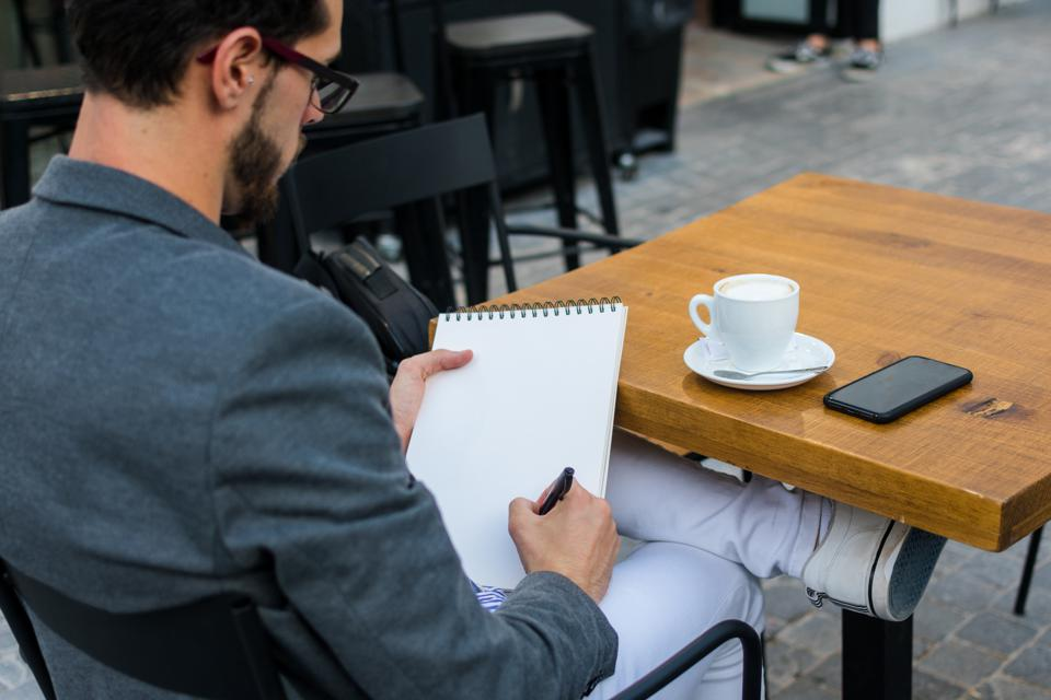 Young businessman is writing in his notebook in a bar terrace