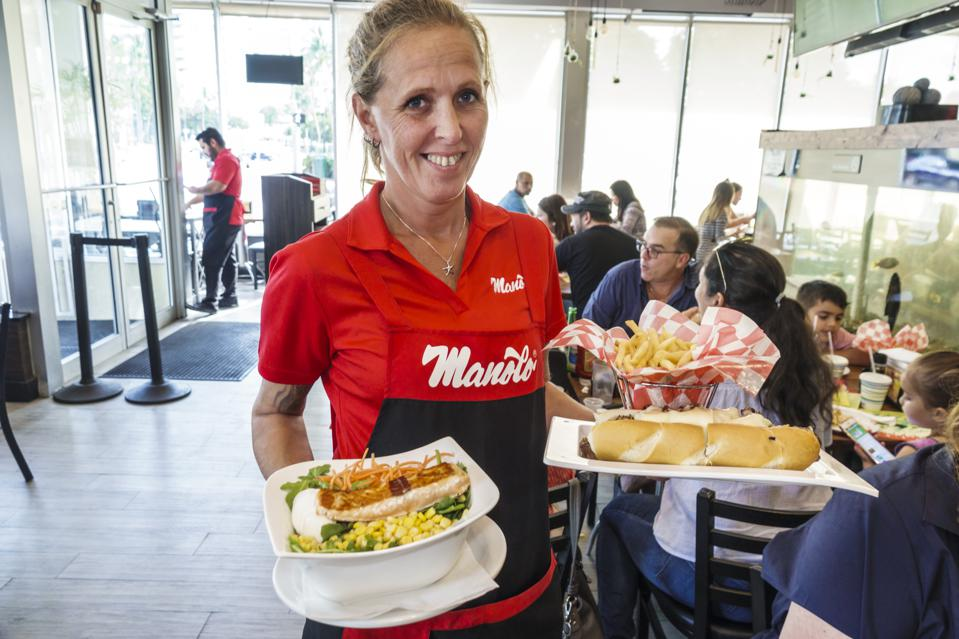Miami Beach, Manolo, Argentinean restaurant, waitress with plates of food