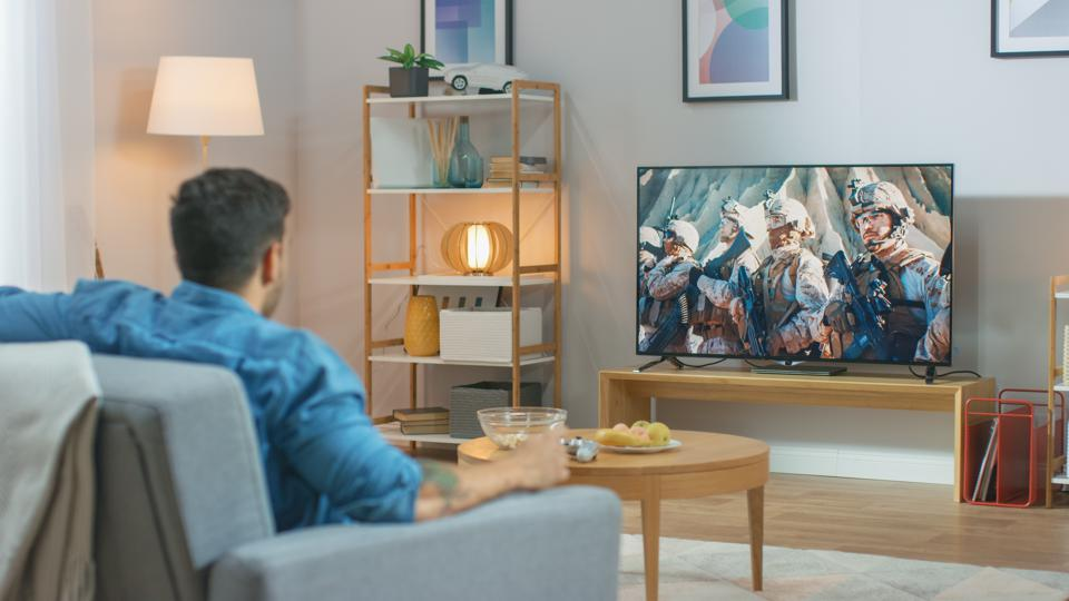 In the Living Room: Guy Relaxing on a Couch Watching War Movie on a TV. Modern Military Warfare Action with War Soldiers Shown on a Television.