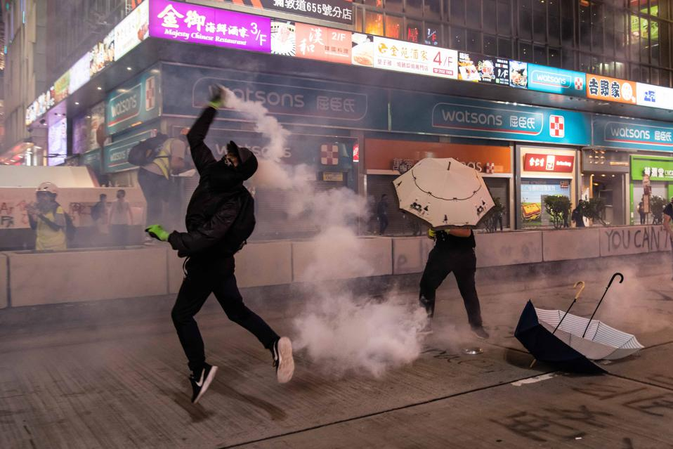 A protestor throws a tear gas canister on October 27 in Hong Kong.
