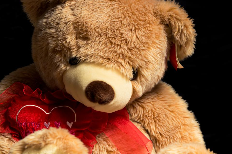 A large valentine holiday teddy bear on a black background. Close up. .