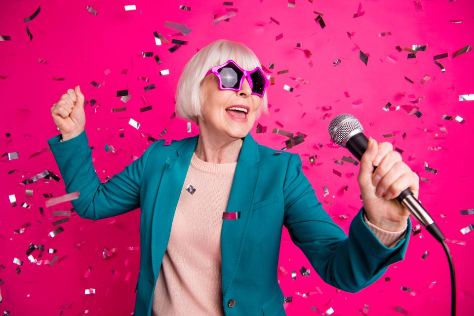 Photo of old mature stylish energetic woman singing in microphone wearing star shaped spectacles standing in falling confetti isolated over pink vivid color background