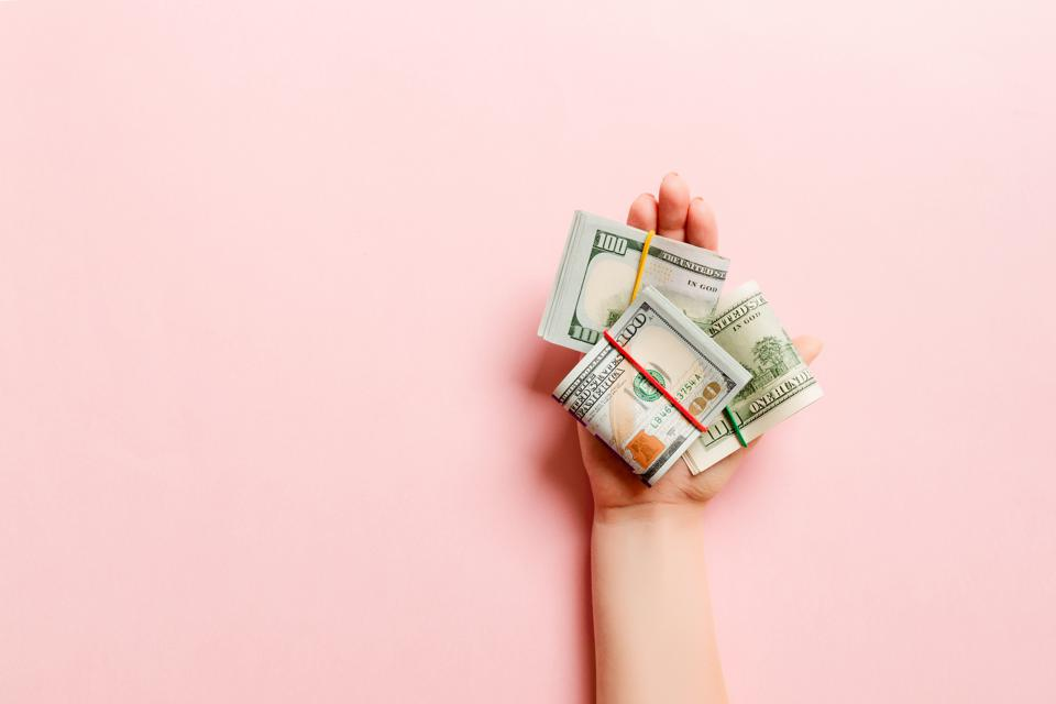 Top view of dollar bills in tubes in female hand on colorful background. Business concept
