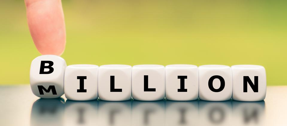 Hand turns a dice and changes the word ″Million″ to Billion″.