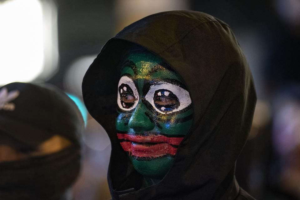 A protester wearing face paint of Pepe the frog in Central...