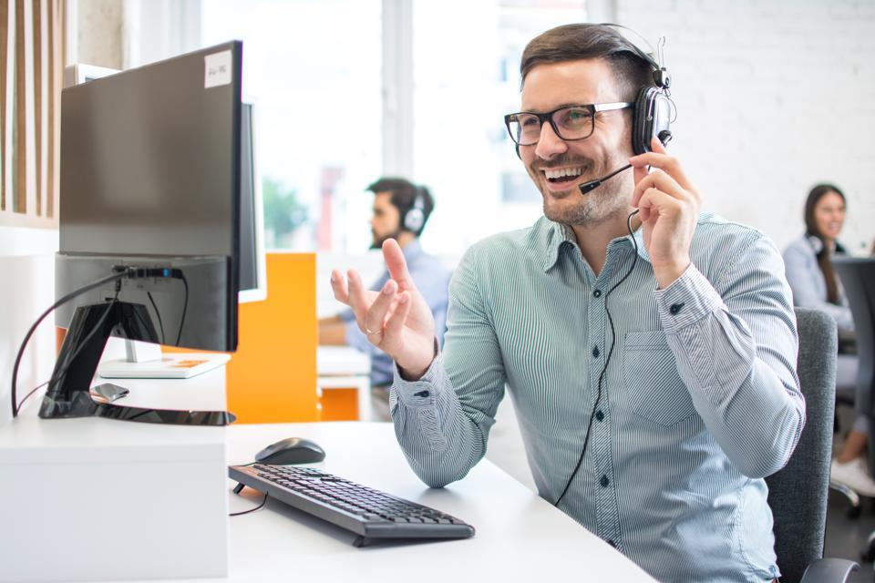 Customer service representative smiling while helping customer.