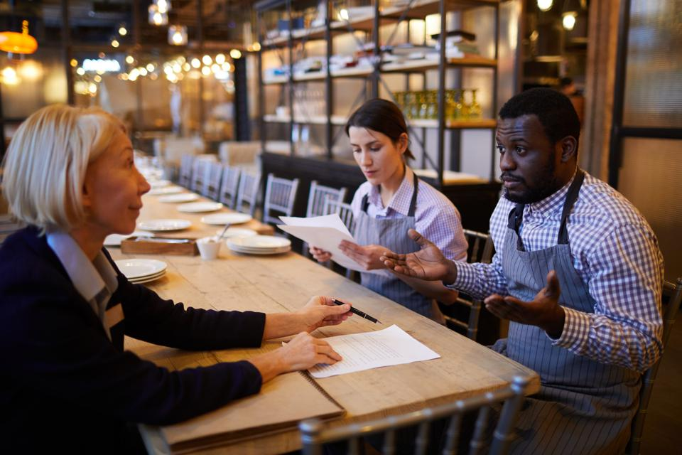 Servers Reading Contract in Restaurant