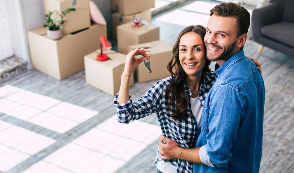 Happy housewarming. A young couple holds happily a key to their new home.