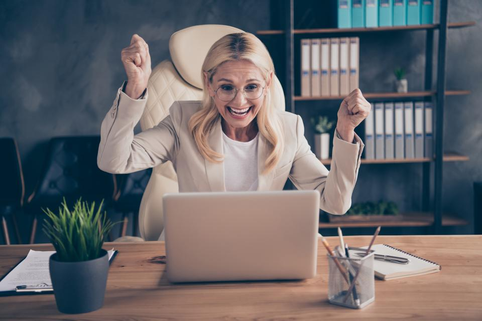 Photo of crazy ecstatic cheerful blonde haired entrepreneur rejoicing with new employee found crazily sitting before laptop looking over project results via wireless connection
