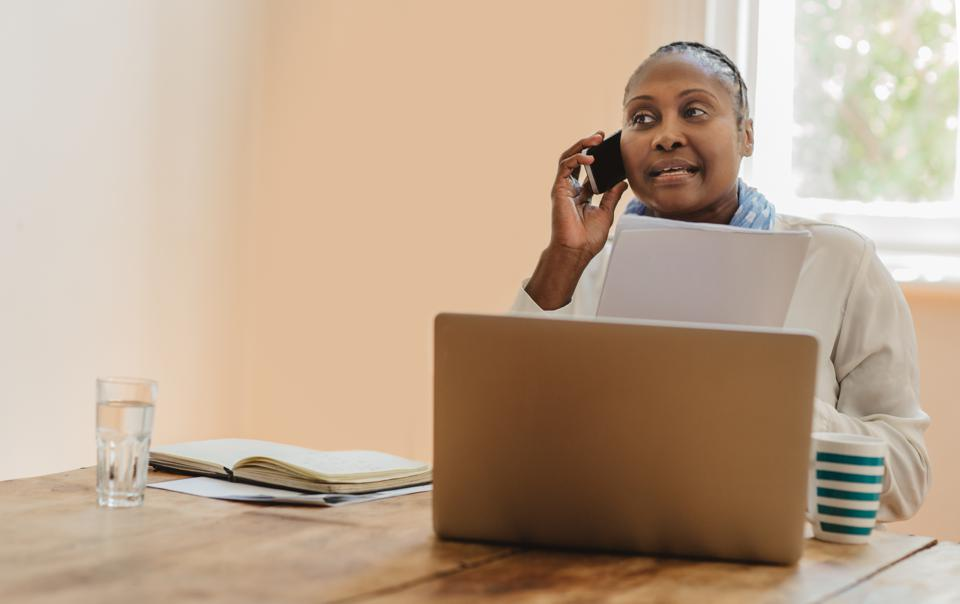 African American businesswoman reading paperwork and talking on her cellphone