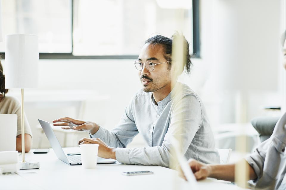 Businessman sharing ideas during team meeting in office conference room